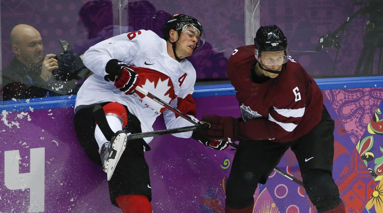 Latvia defenseman Arvids Rekis checks Canada forward Jonathan Toews during the second period of a men's quarterfinal ice hockey game at the 2014 Winter Olympics, Wednesday, Feb. 19, 2014, in Sochi, Russia. (AP Photo/Mark Humphrey)