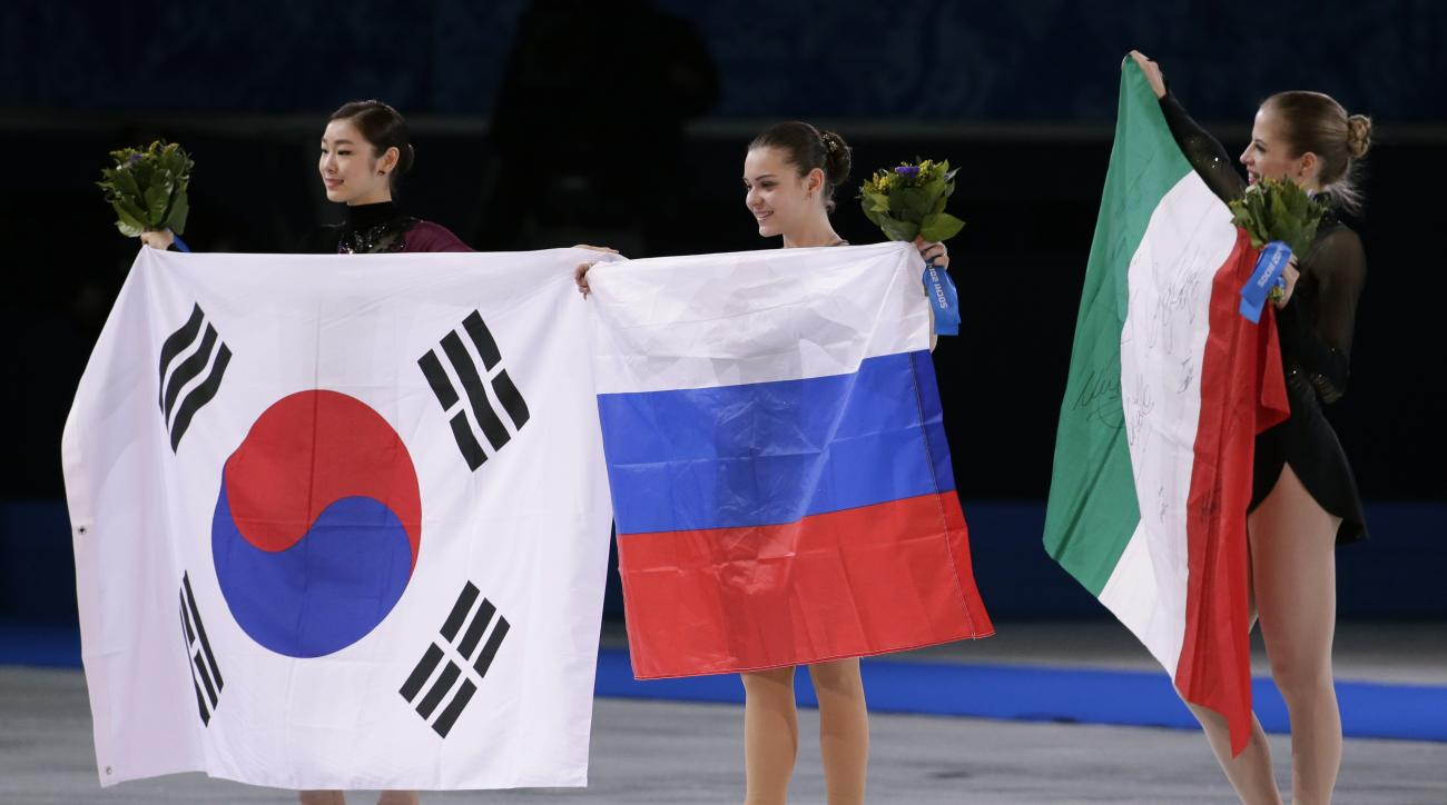 Adelina Sotnikova of Russia, centre, Yuna Kim of South Korea, left, and Carolina Kostner of Italy celebrate with their national flags as they pose for photographers following the flower ceremony for the women's free skate figure skating final at the Iceberg Skating Palace during the 2014 Winter Olympics, Thursday, Feb. 20, 2014, in Sochi, Russia. Sotnikova placed first, followed by Kim and Kostner. (AP Photo/Bernat Armangue)