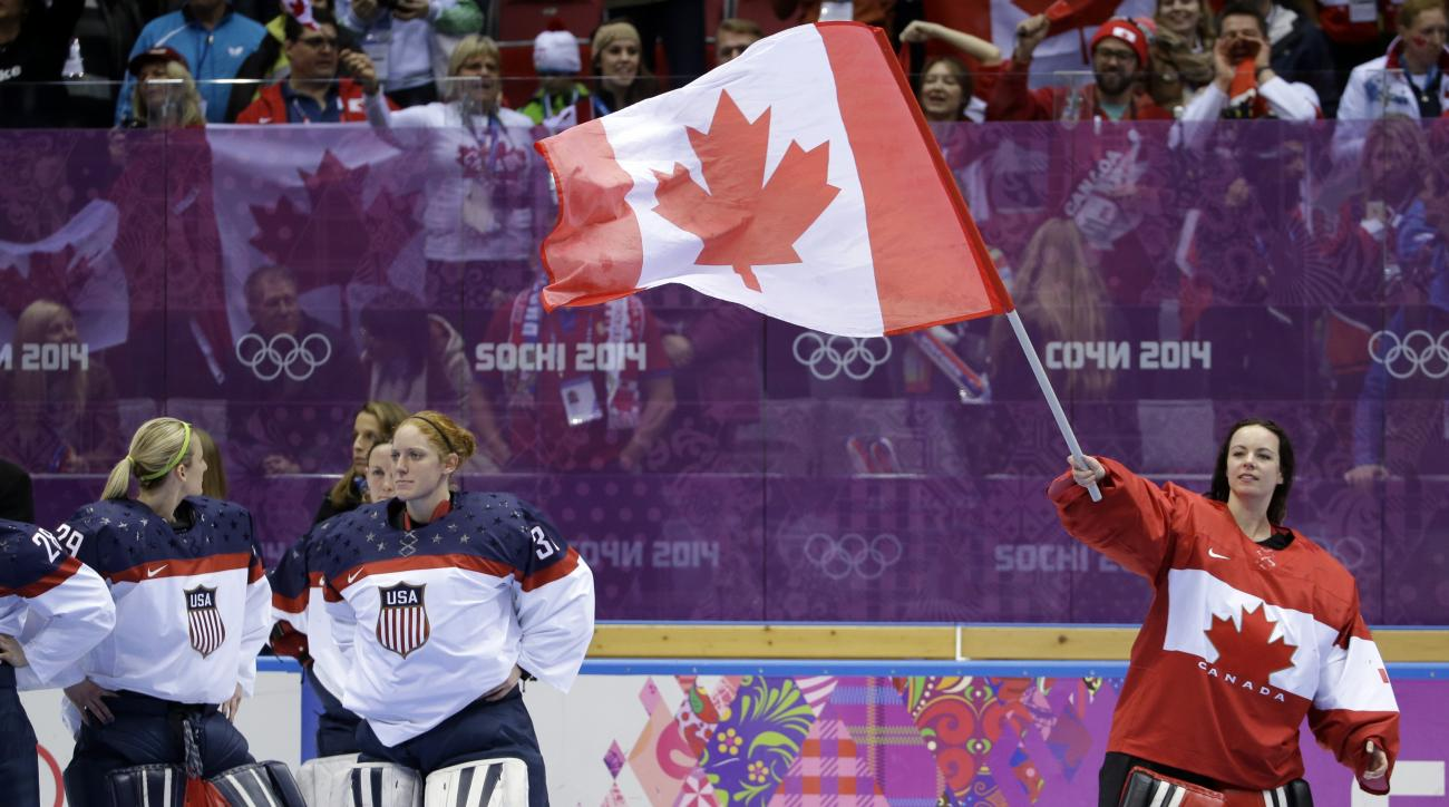Goalkeeper Shannon Szabados of Canada (1) waves the Canadian flag after Canada beat the USA 3-2 in the gold medal women's ice hockey game at the 2014 Winter Olympics, Wednesday, Feb. 19, 2014, in Sochi, Russia. (AP Photo/David Goldman)