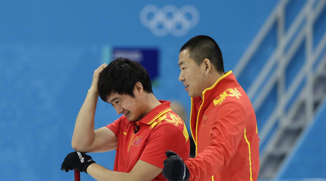 China's Xu Xiaoming, left, and skip Liu Rui, right, watch as their opponents deliver the rock during the men's curling bronze medal game against Sweden at the 2014 Winter Olympics Friday, Feb. 21, 2014, in Sochi, Russia. (AP Photo/Wong Maye-E)