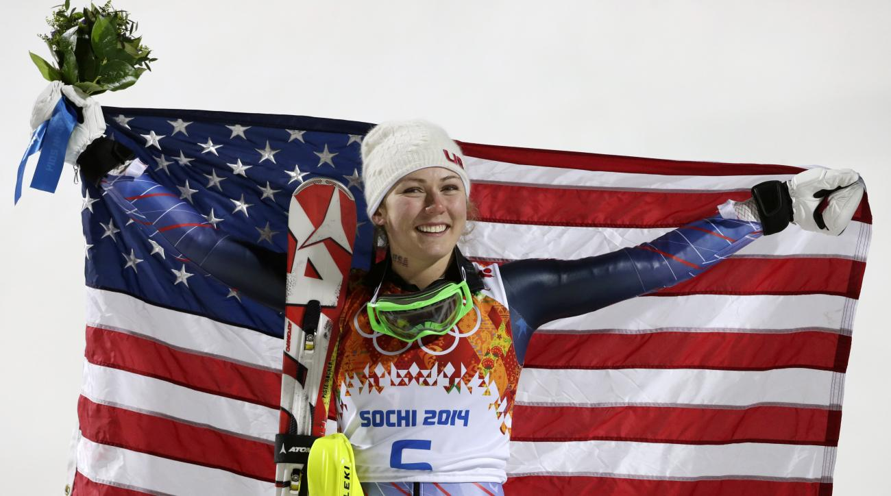 Women's slalom gold medal winner Mikaela Shiffrin of the United States poses for photographers with the U.S. flag at the Sochi 2014 Winter Olympics, Friday, Feb. 21, 2014, in Krasnaya Polyana, Russia.(AP Photo/Gero Breloer)