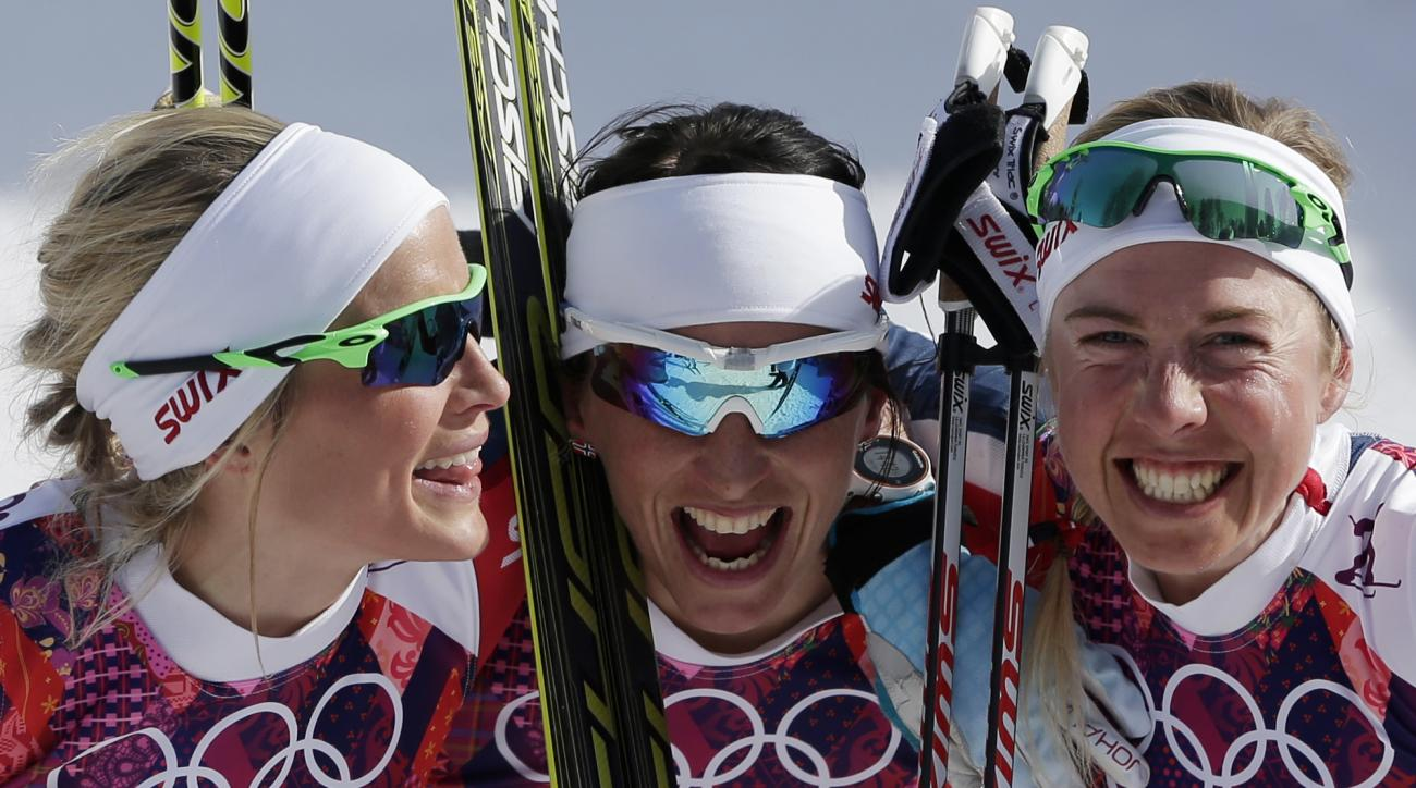 Norway's gold medal winner Marit Bjoergen is flanked by Norway's silver medal winner Therese Johaug, left, and Norway's bronze medal winner Kristin Stoermer Steira, after the women's 30K cross-country race at the 2014 Winter Olympics, Saturday, Feb. 22, 2014, in Krasnaya Polyana, Russia. (AP Photo/Matthias Schrader)