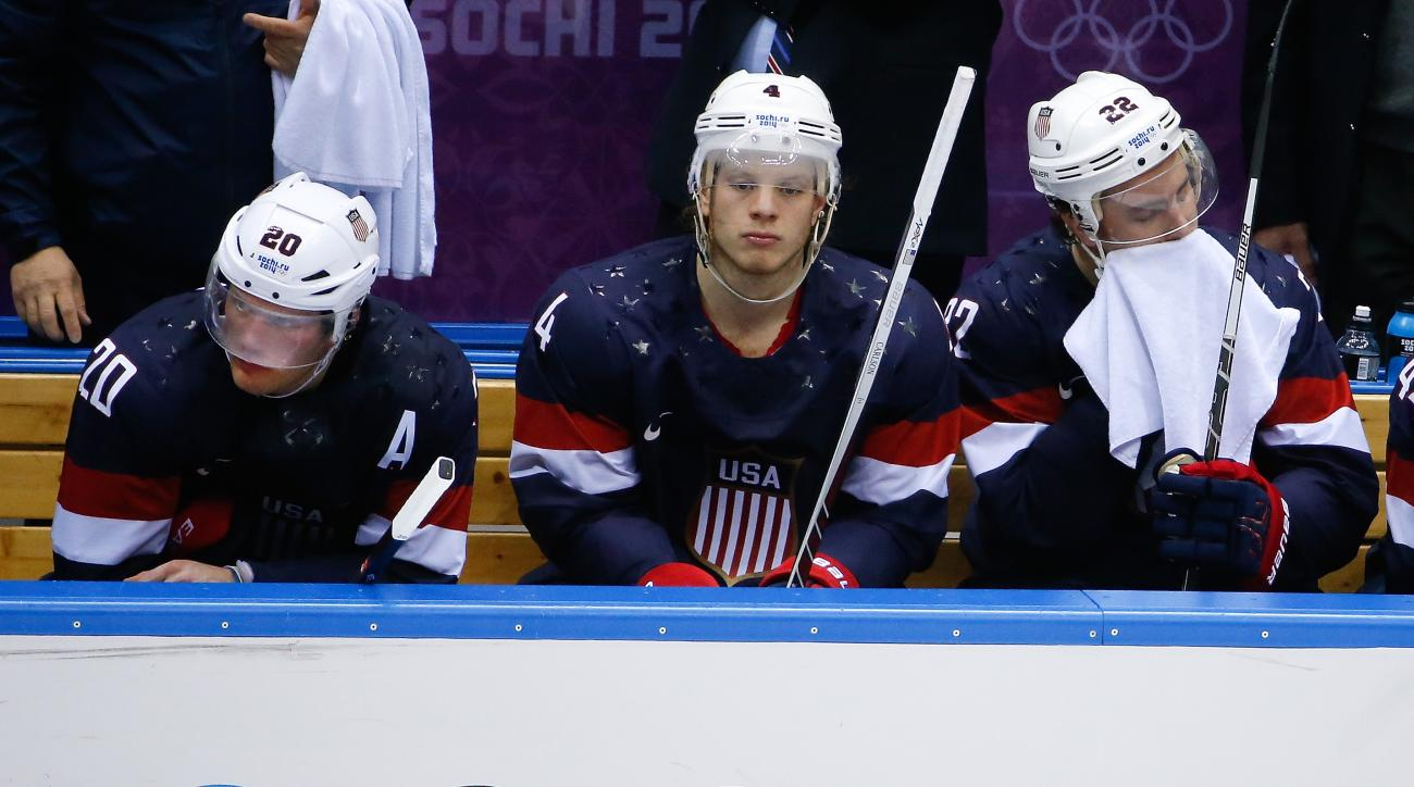 Ryan Suter (20), John Carlson (4) and Kevin Shattenkirk of the United States (22) sit on the bench after Finland scored their fourth goal against the United States during the third period of the men's bronze medal ice hockey game at the 2014 Winter Olympics, Saturday, Feb. 22, 2014, in Sochi, Russia. (AP Photo/Matt Slocum)