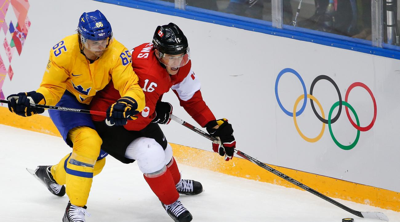 Jonathan Toews of Canada (16) tales control of the puck under pressure from Erik Karlsson of Sweden (65) during the third period of the men's gold medal ice hockey game at the 2014 Winter Olympics, Sunday, Feb. 23, 2014, in Sochi, Russia. (AP Photo/Petr David Josek)
