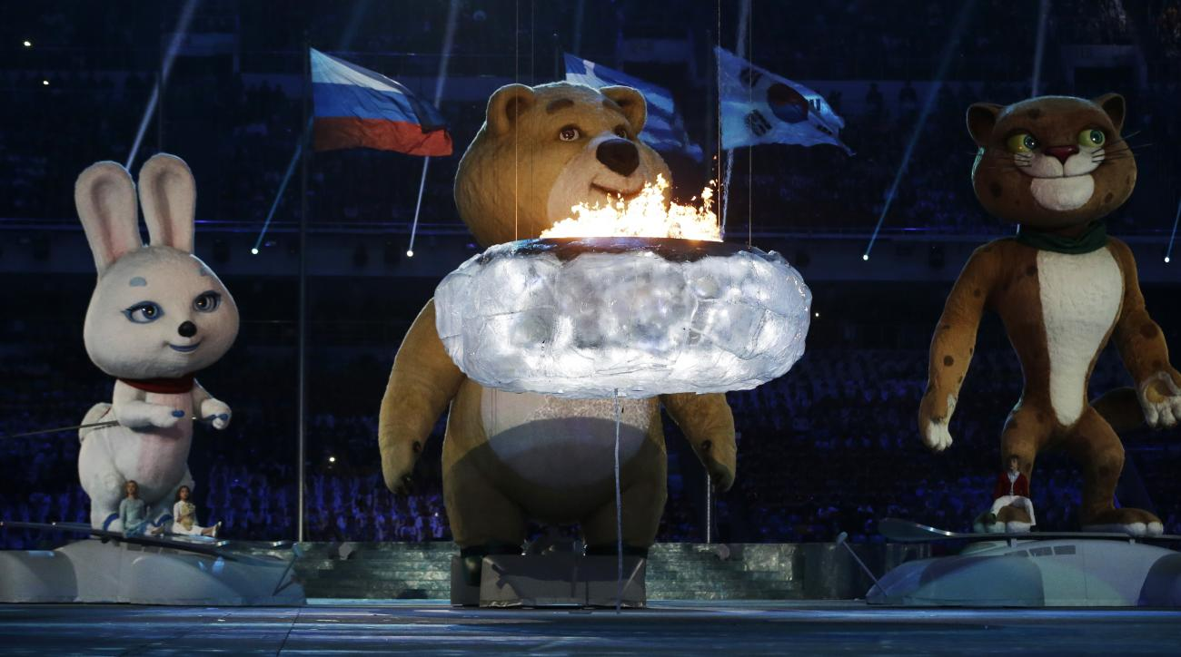 Giant robotic mascots gather around the Olympic flame before extinguishing it during the closing ceremony of the 2014 Winter Olympics, Sunday, Feb. 23, 2014, in Sochi, Russia. (AP Photo/Darron Cummings)
