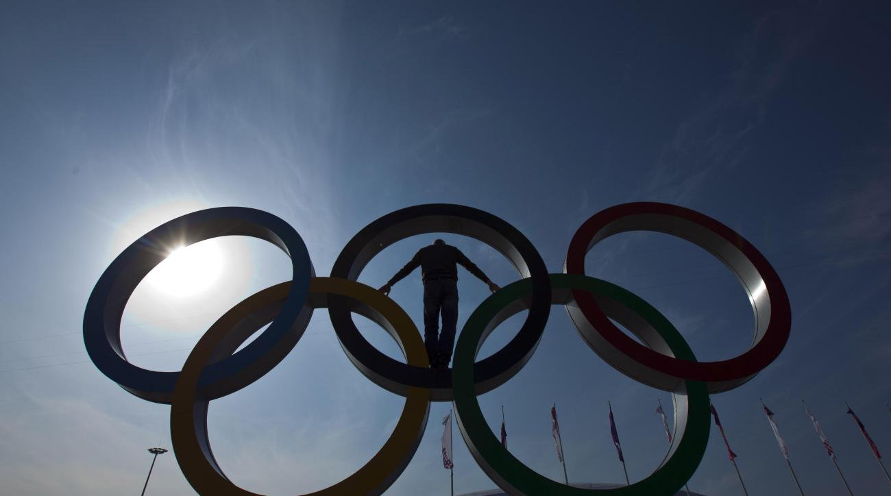 A visitor poses on the Olympic rings after the 2014 Winter Olympics, Monday, Feb. 24, 2014, in Sochi, Russia. (AP Photo/Matt Slocum)