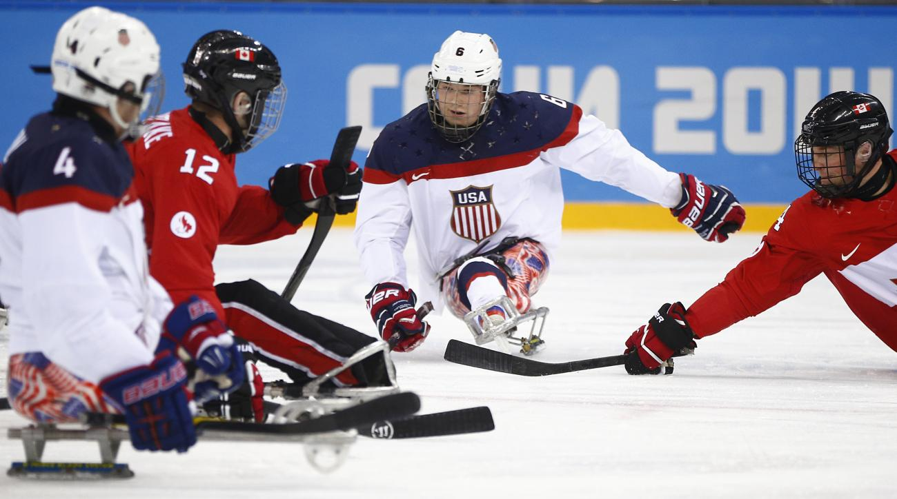 United States' Declan Farmer, center, in action during the ice sledge hockey semifinal match against Canada at the 2014 Winter Paralympics in Sochi, Russia, Thursday, March 13, 2014. United States won 3-0. (AP Photo/Pavel Golovkin)