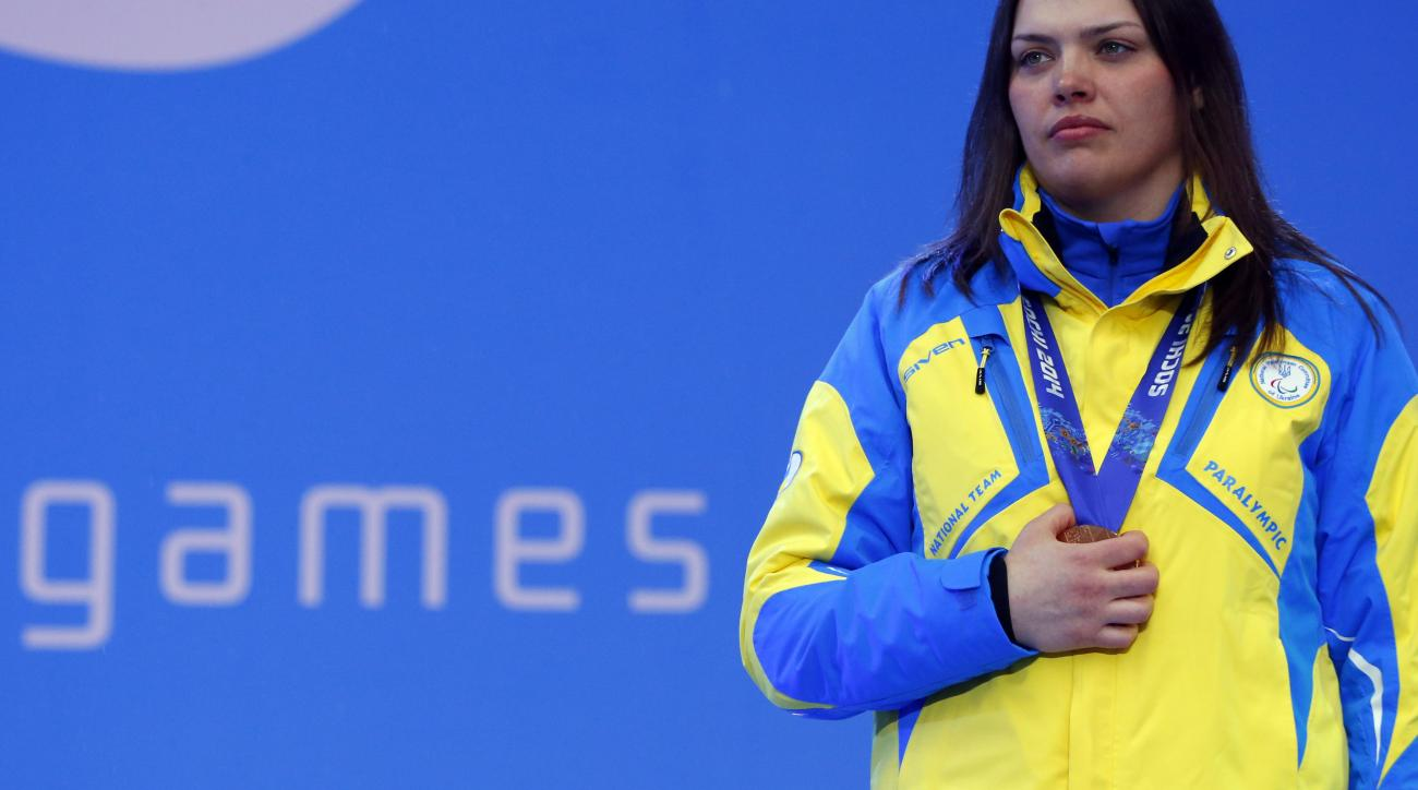 Ukraine's Olena Iurkovska covers her bronze medal with her hand after finishing third in the women's biathlon 12,5 km sitting during a medal ceremony at the 2014 Winter Paralympics, Friday, March 14, 2014, in Krasnaya Polyana, Russia. The majority of Ukraine's Paralympic medalists covered their medals during medal ceremonies. (AP Photo/Dmitry Lovetsky)