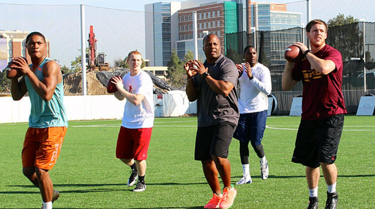 George Whitfield (center) instructs Jerrod Heard, Gavin McCarney, Marquise Williams and Taylor Kelly.