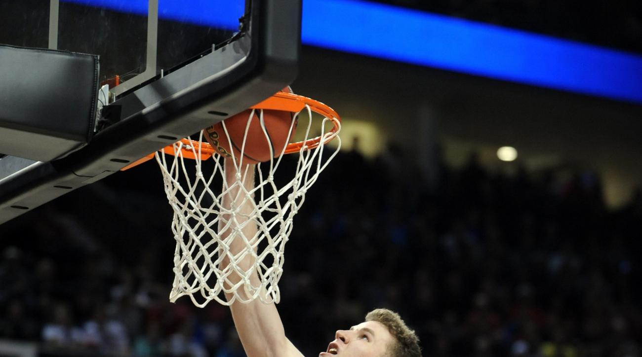 Utah guard Jakob Poeltl, left, scores against Georgetown forward Paul White during the second half of an NCAA college basketball tournament round of 32 game in Portland, Ore., Saturday, March 21, 2015. (AP Photo/Greg Wahl-Stephens)