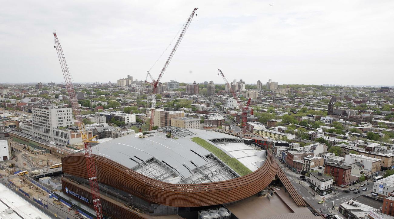 In this May 6, 2015, photo, construction continues on a new roof for the Barclays Center in the Brooklyn borough of New York. A construction project is underway atop the Barclays Center to replace the sprawling over 130,000-square-foot roof with panels of