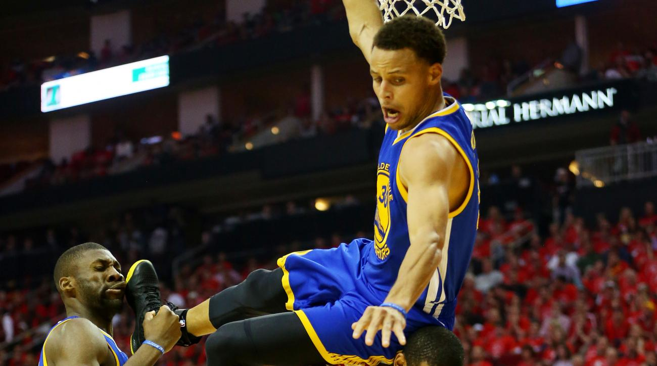 HOUSTON, TX - MAY 25:  Stephen Curry #30 of the Golden State Warriors falls over Trevor Ariza #1 of the Houston Rockets on his way to an injury in the second quarter during Game Four of the Western Conference Finals of the 2015 NBA Playoffs at Toyota Cent