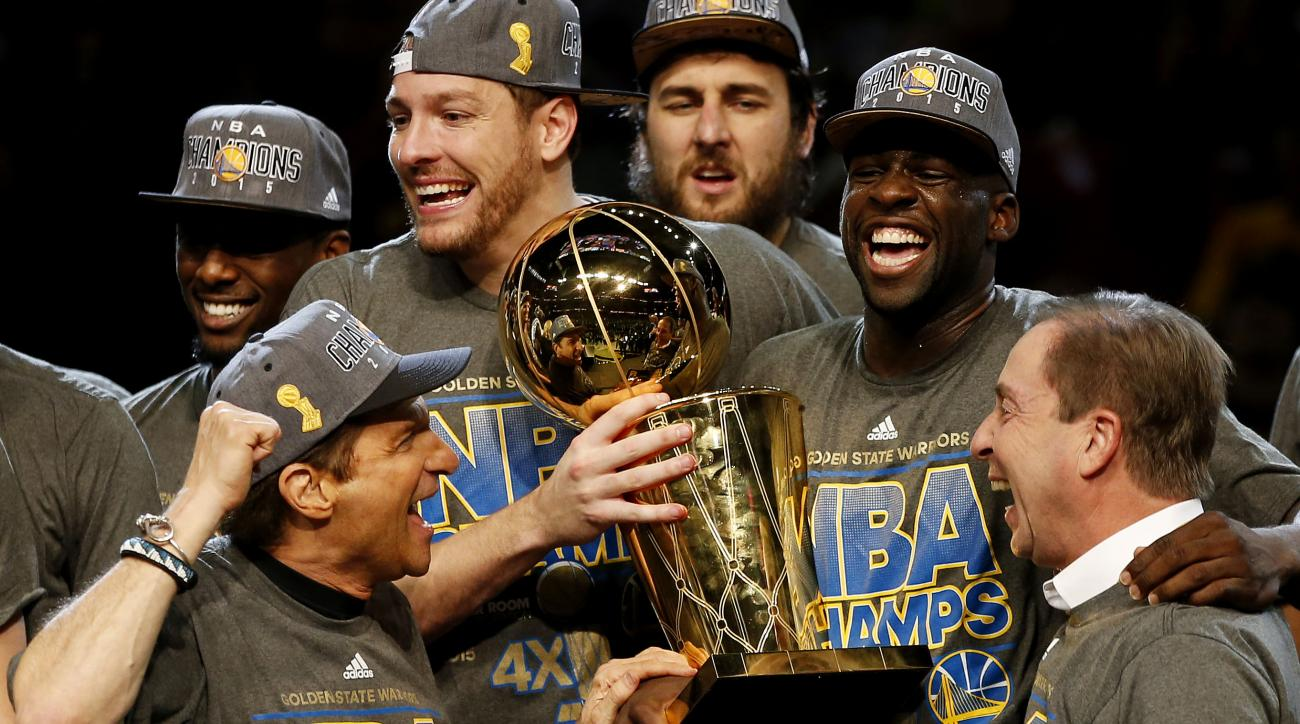 CLEVELAND, OH - JUNE 16:  Draymond Green #23 David Lee #10 and Andrew Bogut #12 of the Golden State Warriors celebrates with team owners Peter Guber and Joe Lacob and the Larry O'Brien NBA Championship Trophy after defeating the Cleveland Cavaliers 105 to
