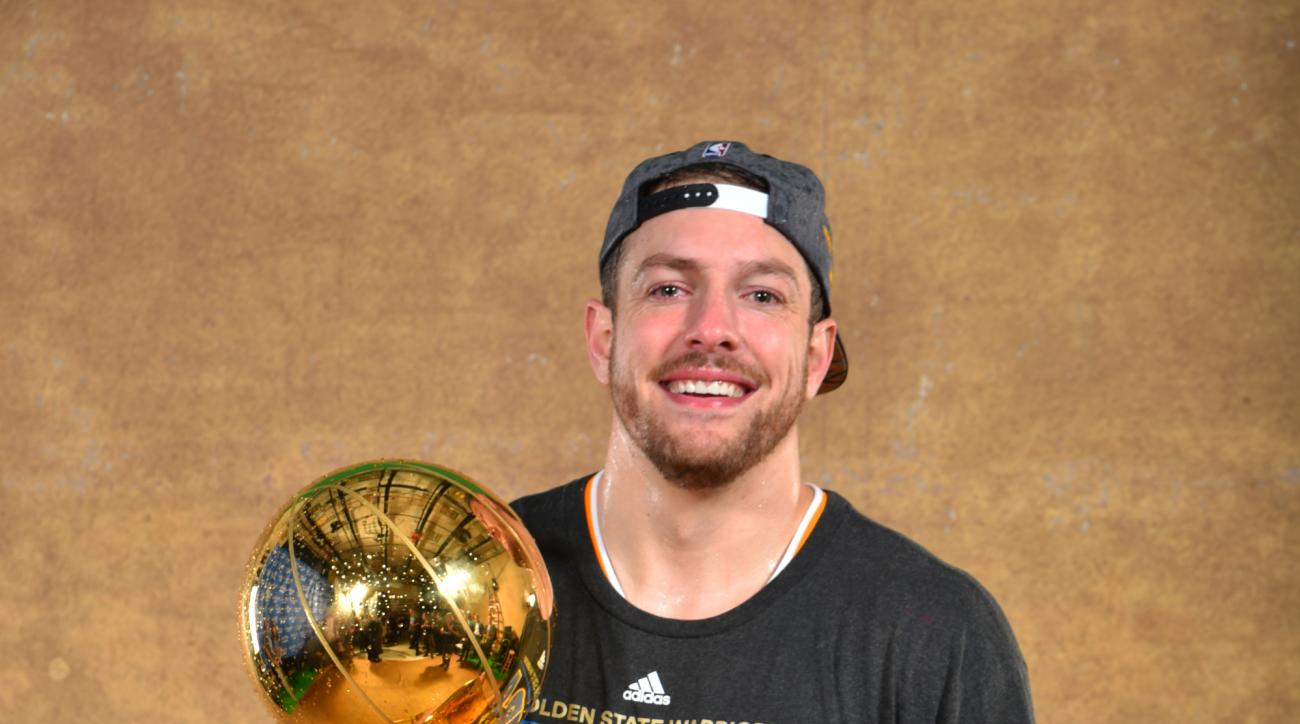 CLEVELAND, OH - JUNE 16: David Lee #10 of the Golden State Warriors poses for a portrait with the Larry O'Brien trophy after defeating the Cleveland Cavaliers in Game Six of the 2015 NBA Finals on June 16, 2015 at Quicken Loans Arena in Cleveland, Ohio. (