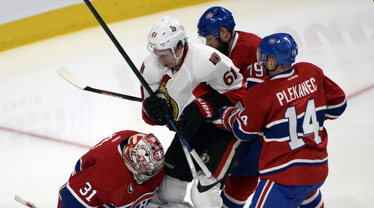 Ottawa Senators right wing Mark Stone (61) is checked into Montreal Canadiens goalie Carey Price (31) by Montreal Canadiens center Tomas Plekanec (14) and Montreal Canadiens defenseman Andrei Markov (79) during second period of the NHL Stanley Cup first r