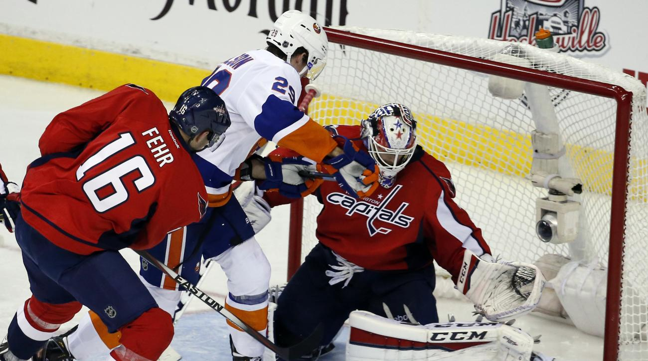 Washington Capitals right wing Eric Fehr (16) defends with goalie Braden Holtby (70) as New York Islanders center Brock Nelson (29) works in front of the net during the third period in the opening game of a first-round NHL hockey playoff series, Wednesday