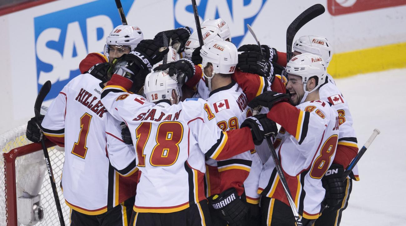 The Calgary Flames celebrate their 2-1 win over the Vancouver Canucks in Game 1 of an NHL hockey first-round playoff series, Wednesday, April 15, 2015, in Vancouver, British Columbia.  (Jonathan Hayward/The Canadian Press via AP)