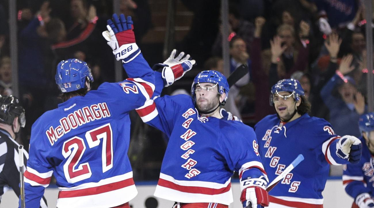 New York Rangers' Ryan McDonagh, left, celebrates with teammate Keith Yandle, center, and Mats Zuccarello, right, during the first period of Game 1 in the first round of the NHL hockey Stanley Cup playoffs Thursday, April 16, 2015, in New York.  (AP Photo