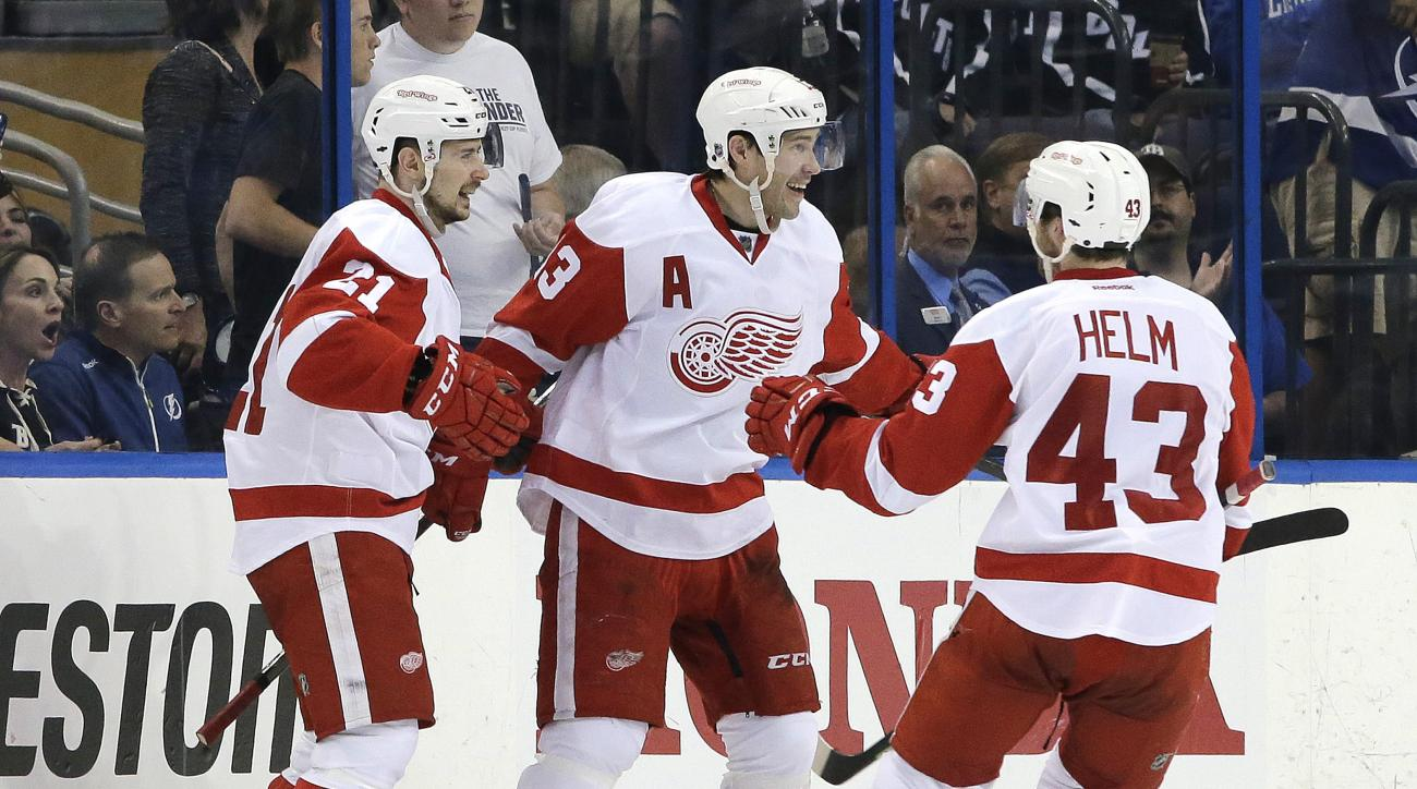 Detroit Red Wings center Pavel Datsyuk (13), of Russia, celebrates his goal against the Tampa Bay Lightning with left wing Tomas Tatar (21), of Slovakia, and center Darren Helm (43) during the second period of Game 1 of an NHL hockey first-round playoff s