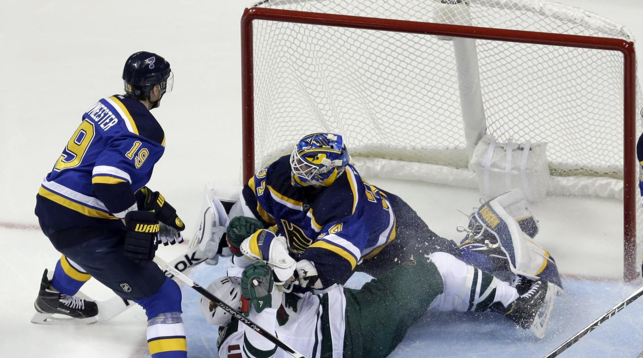 Minnesota Wild's Zach Parise, bottom right, slides into St. Louis Blues goalie Jake Allen as Blues' Jay Bouwmeester, left, watches during the second period in Game 1 of an NHL hockey first-round playoff series, Thursday, April 16, 2015, in St. Louis. Bouw