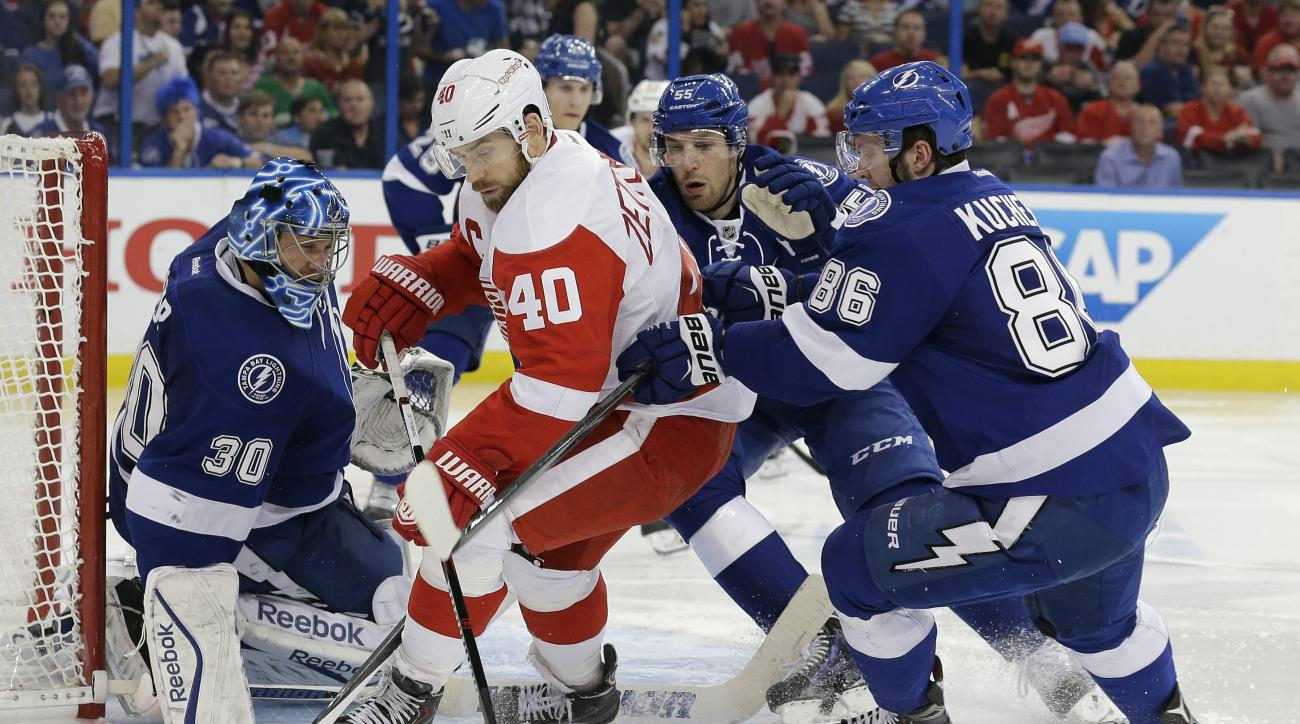 Detroit Red Wings left wing Henrik Zetterberg (40), of Sweden, is stopped by Tampa Bay Lightning goalie Ben Bishop (30), defenseman Braydon Coburn (55) and right wing Nikita Kucherov (86), of Russia, during the third period of Game 2 of a first-round NHL