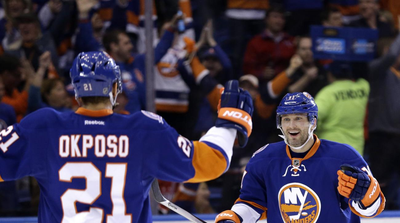 New York Islanders' Lubomir Visnovsky, right, celebrates with Kyle Okposo (21) after Okposo scored during the second period of Game 3 of a first-round NHL hockey playoff series against the Washington Capitals, Sunday, April 19, 2015, in Uniondale, New Yor