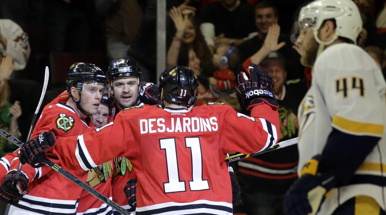 Chicago Blackhawks defenseman Brent Seabrook, second from right, celebrates with center Jonathan Toews, left, center Andrew Shaw and center Andrew Desjardins (11) after scoring his goal as Nashville Predators defenseman Cody Franson (44) reacts during the