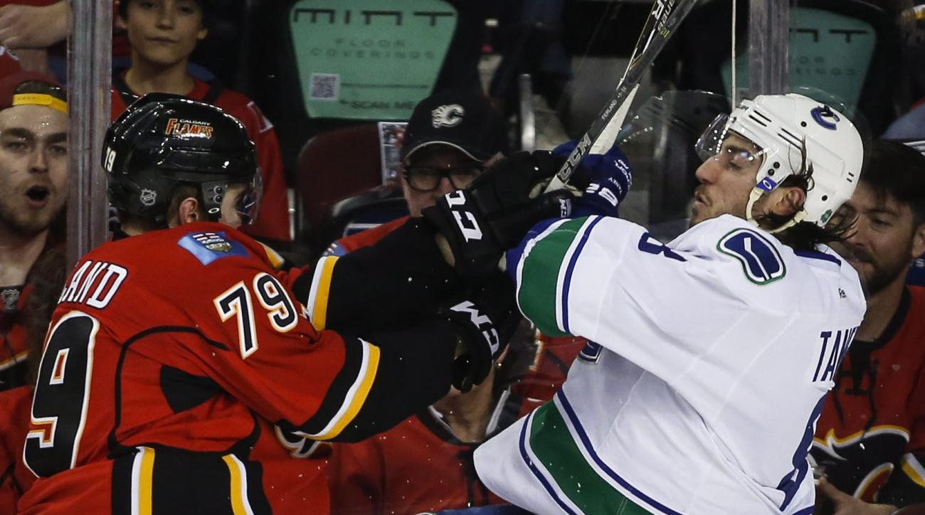Vancouver Canucks' Chris Tanev, right, checks Calgary Flames Michael Ferland during second period NHL first round playoff hockey action in Calgary, Sunday, April 19, 2015. (Jeff McIntosh/The Canadian Press via AP) MANDATORY CREDIT