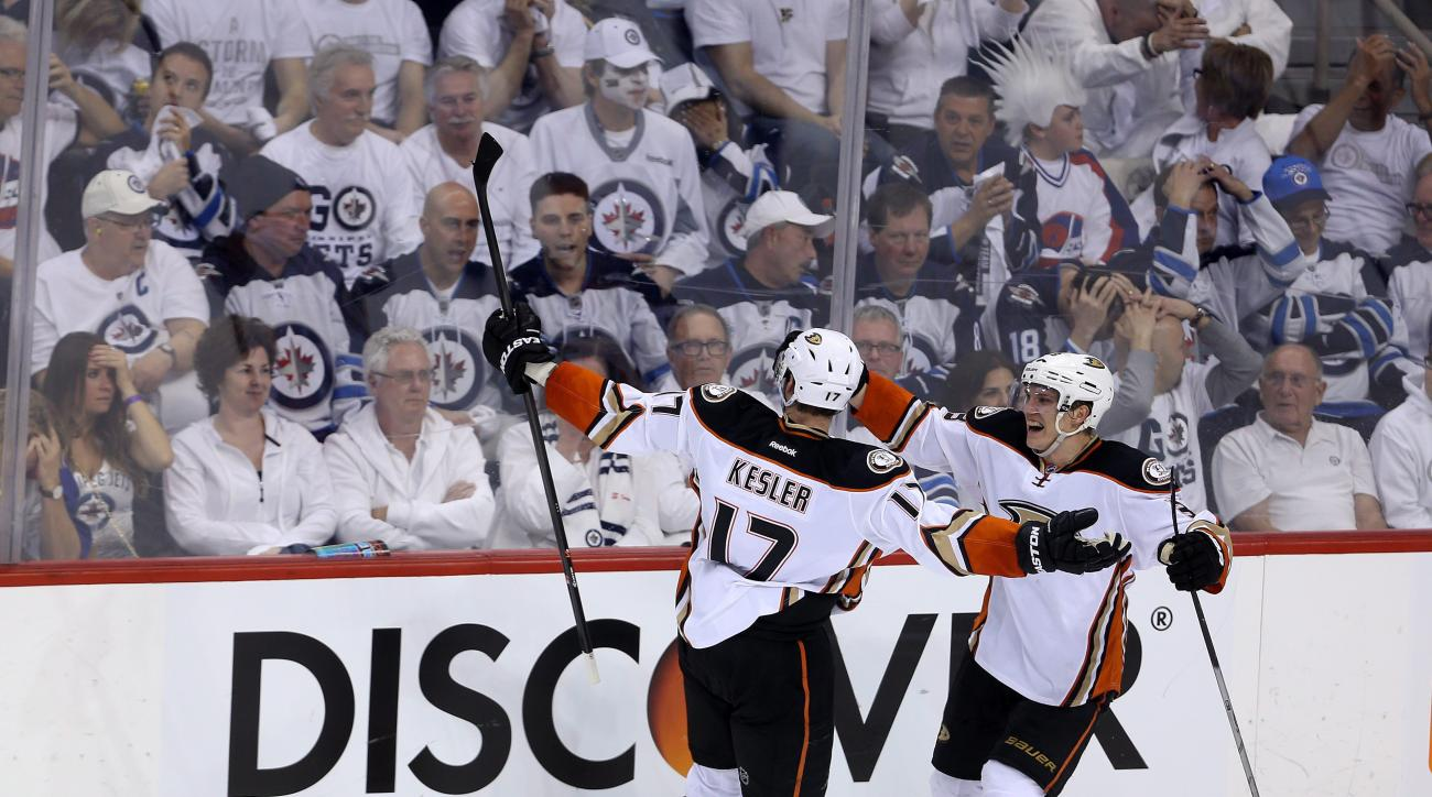 Anaheim Ducks Ryan Kesler (17) celebrates with Jakob Silfverberg (33) after scoring against the Winnipeg Jets during the third period of game three NHL playoff hockey action in Winnipeg, Monday, April 20, 2015. (Trevor Hagan/The Canadian Press via AP)   M