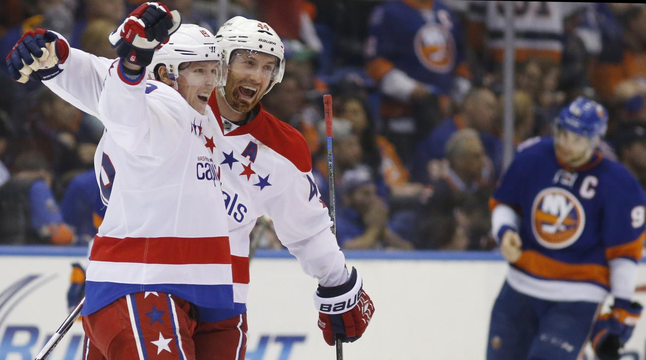 Washington Capitals defenseman Brooks Orpik (44) celebrates with Capitals center Nicklas Backstrom (19) of Sweden as New York Islanders center John Tavares (91) leaves the ice with his head down after Backstrom scored in overtime of Game 4 of a first-roun