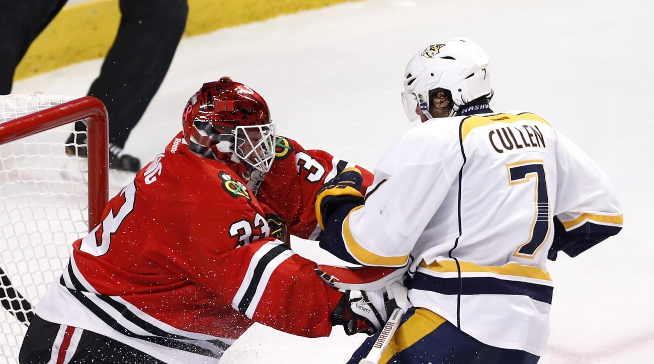 Chicago Blackhawks goalie Scott Darling (33) pushes back on Nashville Predators center Matt Cullen as Cullen slides into the crease during the second period in Game 4 of an NHL Western Conference hockey playoff series Tuesday, April 21, 2015, in Chicago.