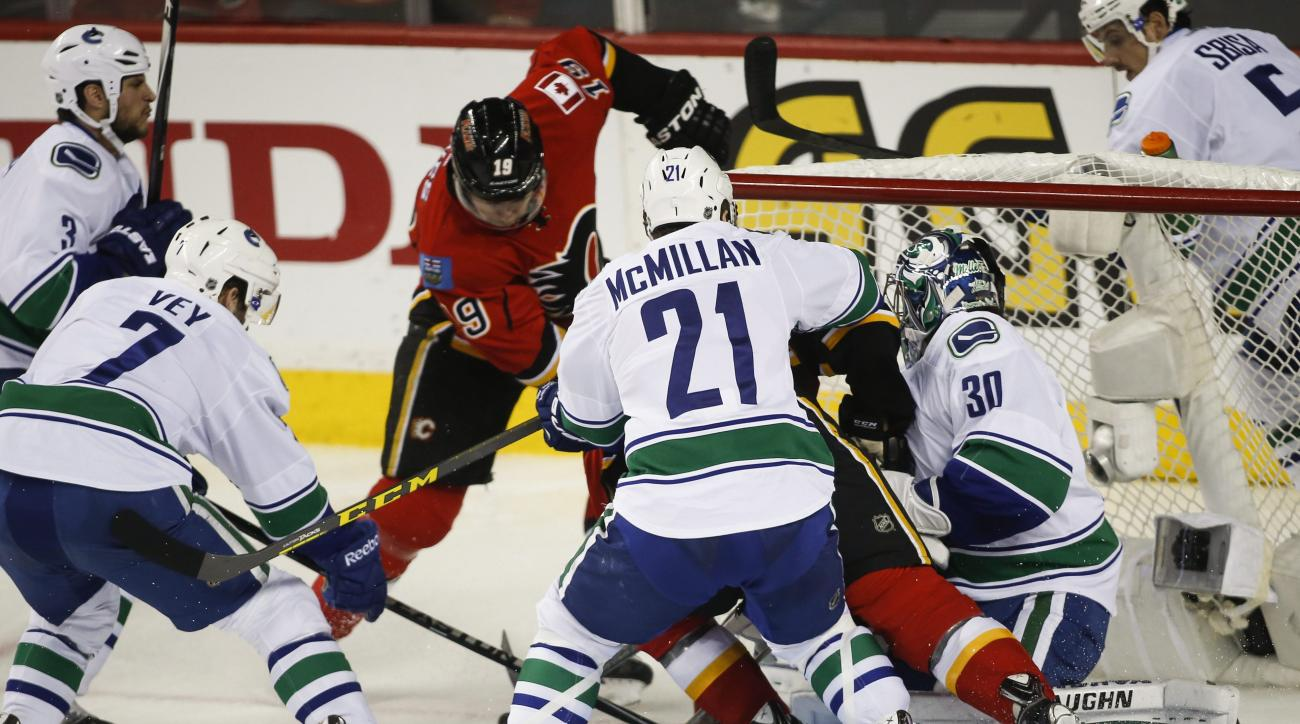 Vancouver Canucks goalie Ryan Miller, right, gets shoved into the net during a fracas with the Calgary Flames during the second period of Game 4 of a first-round NHL hockey playoff series, Tuesday, April 21, 2015, in Calgary, Alberta. (Jeff McIntosh/The C