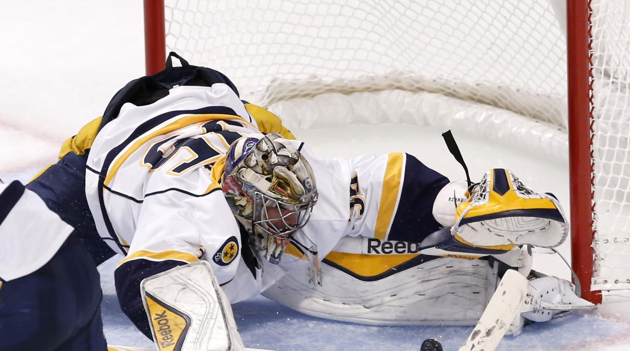 Nashville Predators goalie Pekka Rinne makes a save during the first overtime period in Game 4 of an NHL Western Conference hockey playoff series against the Chicago Blackhawks on Wednesday, April 22, 2015, in Chicago. (AP Photo/Charles Rex Arbogast)