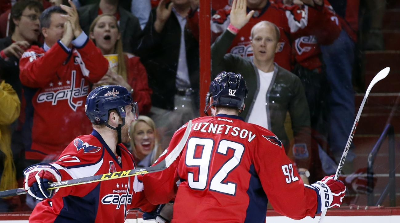 Washington Capitals defenseman Karl Alzner (27) and center Evgeny Kuznetsov (92), from Russia, celebrate Kuznetsov's goal during the first period of Game 5 in the first round of the NHL hockey Stanley Cup playoffs against the New York Islanders, Thursday,