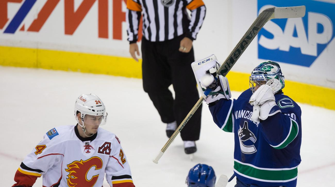 Calgary Flames' Jiri Hudler, left, of the Czech Republic, skates away as Vancouver Canucks goalie Ryan Miller celebrates after the Canucks defeated the Flames 2-1 in Game 5 of an NHL hockey first-round playoff series, Thursday, April 23, 2015, in Vancouve