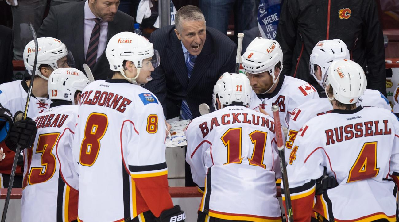 Calgary Flames coach Bob Hartley, center, speaks to his players during a timeout during the third period against the Vancouver Canucks in Game 5 of an NHL hockey first-round playoff series, Thursday, April 23, 2015, in Vancouver, British Columbia. (Darryl