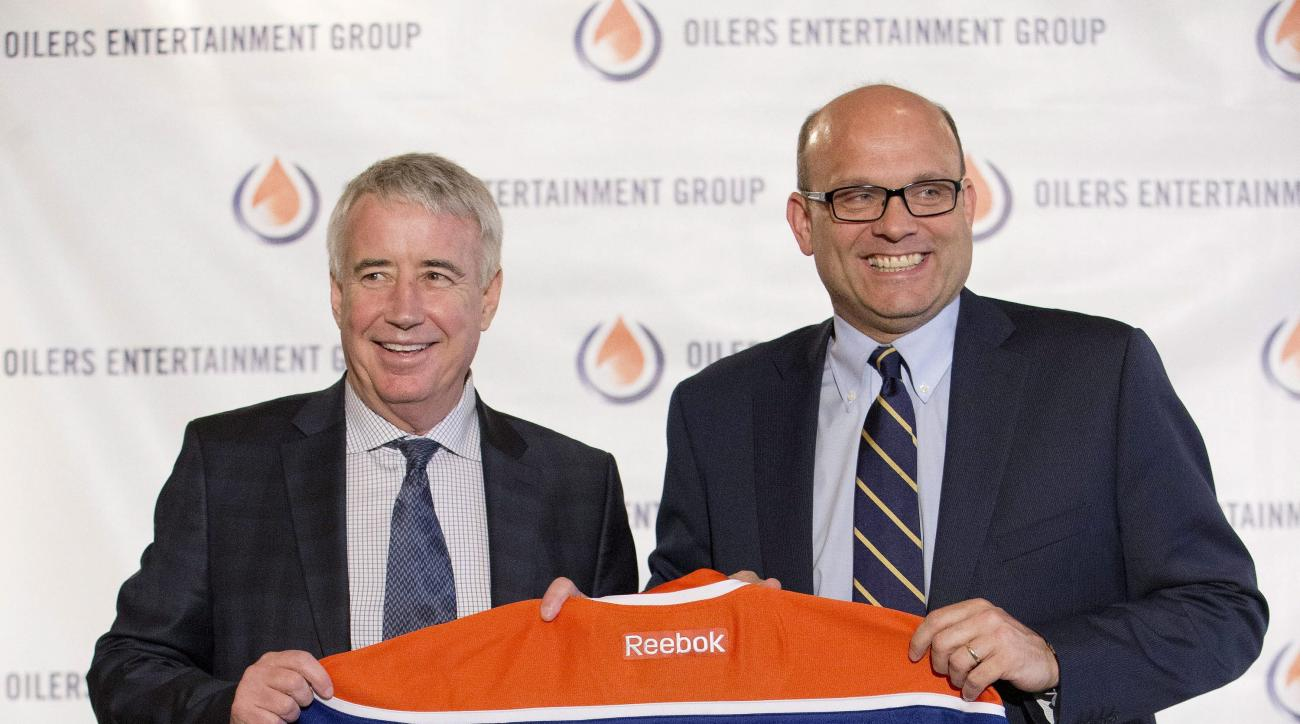 Edmonton Oilers CEO Bob Nicholson, left, and new President and General Manager Peter Chiarelli hold up an Oilers jersey with Chiarelli's name on it during an NHL hockey press conference in Edmonton, Alberta, Friday April 24, 2015. (Jason Franson/The Canad