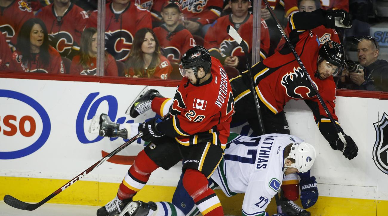 Vancouver Canucks' Shawn Matthias, lower right, is checked by Calgary Flames' David Jones, right, and Tyler Wotherspoon during the first period of Game 6 of a first-round NHL hockey playoff series, Saturday, April 25, 2015, in Calgary, Alberta. (Jeff McIn