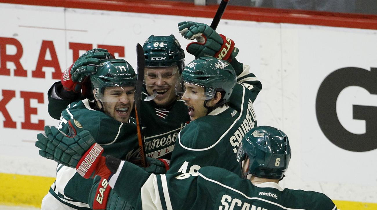 Minnesota Wild left wing Zach Parise, left, celebrates with teammates center Mikael Granlund (64), of Finland, defenseman Jared Spurgeon, and defenseman Marco Scandella (6) after Parise's goal on St. Louis Blues goalie Jake Allen during the first period o