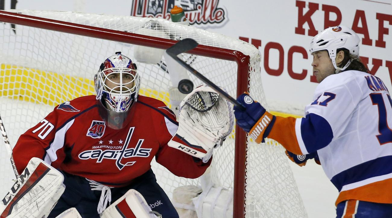 Washington Capitals goalie Braden Holtby (70) keeps his eye on the puck as New York Islanders left wing Matt Martin (17) attempts to deflect it during the third period of Game 7 in the first round of the NHL hockey Stanley Cup playoffs, Monday, April 27,