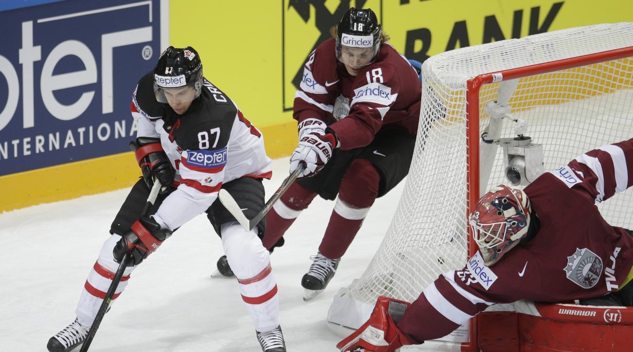 Canada's Sidney Crosby, left, controls a puck past Latvia's Rodrigo Abols, center, and Latvia's  Ervins Mustukovs, right, during the Hockey World Championships Group A in Prague, Czech Republic, Friday, May 1, 2015. (AP Photo/Petr David Josek)