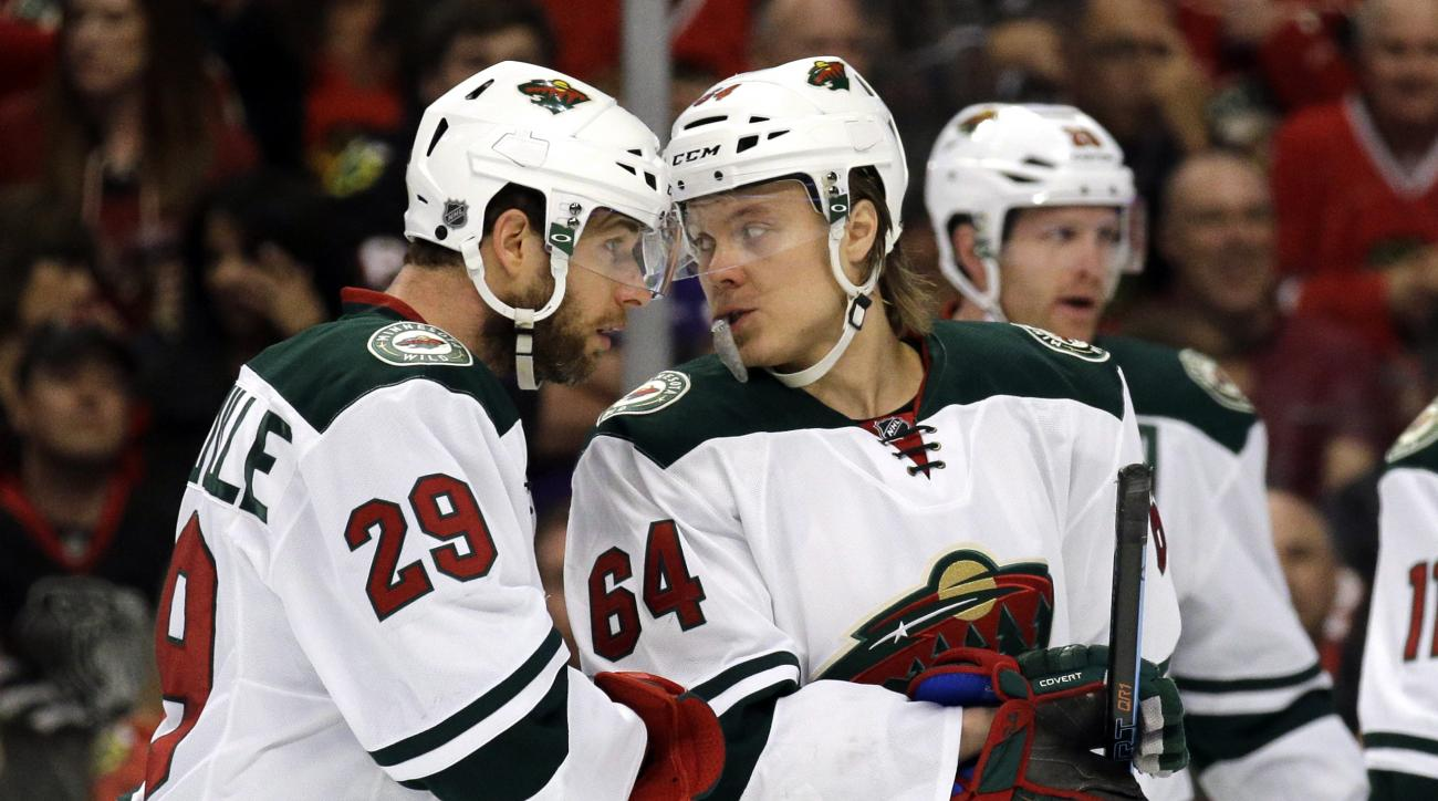 Minnesota Wild right wing Jason Pominville, left, listens to center Mikael Granlund during the first period  of Game 2 in the second round of the NHL Stanley Cup hockey playoffs against the Chicago Blackhawks in Chicago, Sunday, May 3, 2015. (AP Photo/Nam