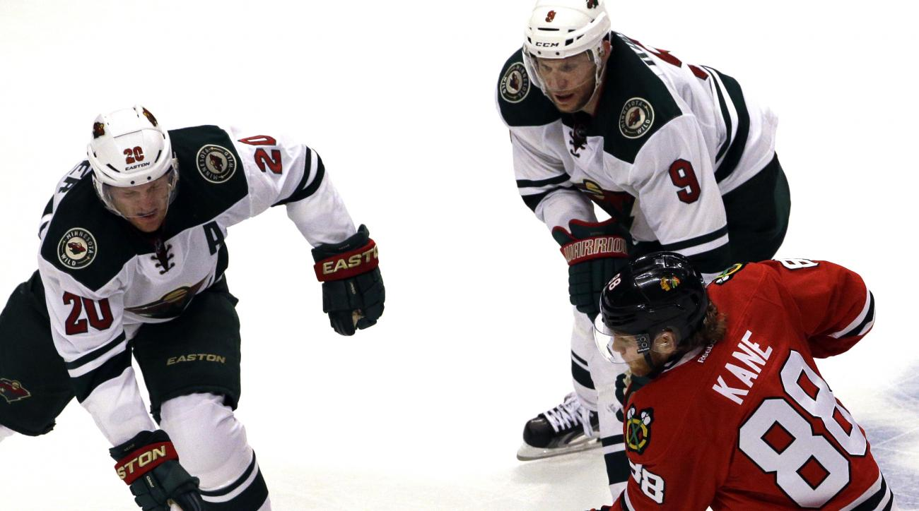 Chicago Blackhawks right wing Patrick Kane (88) shoots against Minnesota Wild defenseman Ryan Suter (20) and center Mikko Koivu (9) during the third period  of Game 2 in the second round of the NHL Stanley Cup hockey playoffs in Chicago, Sunday, May 3, 20