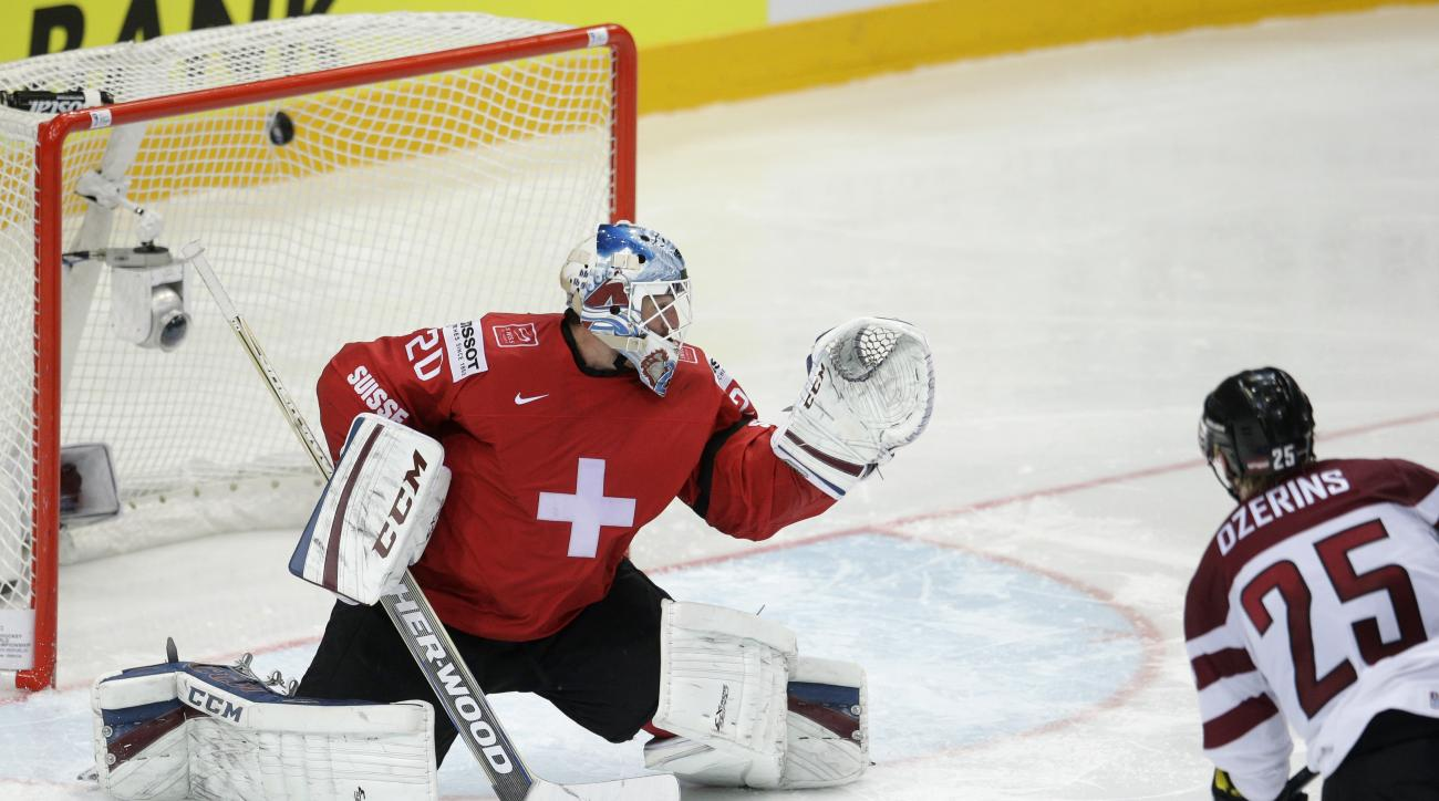 Latvia's Andris Dzerins, right, shoots to score past Switzerland's Reto Berra, left, during the Hockey World Championships Group A match in Prague, Czech Republic, Wednesday, May 6, 2015. (AP Photo/Petr David Josek)