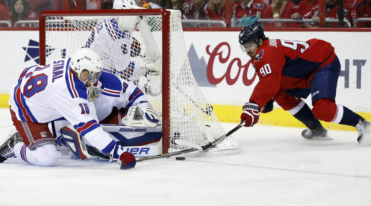 Washington Capitals left wing Marcus Johansson (90), from Sweden, reaches for a shot as New York Rangers defenseman Marc Staal (18) and goalie Henrik Lundqvist, from Sweden, defend during the first period of Game 4 in the second round of the NHL Stanley C