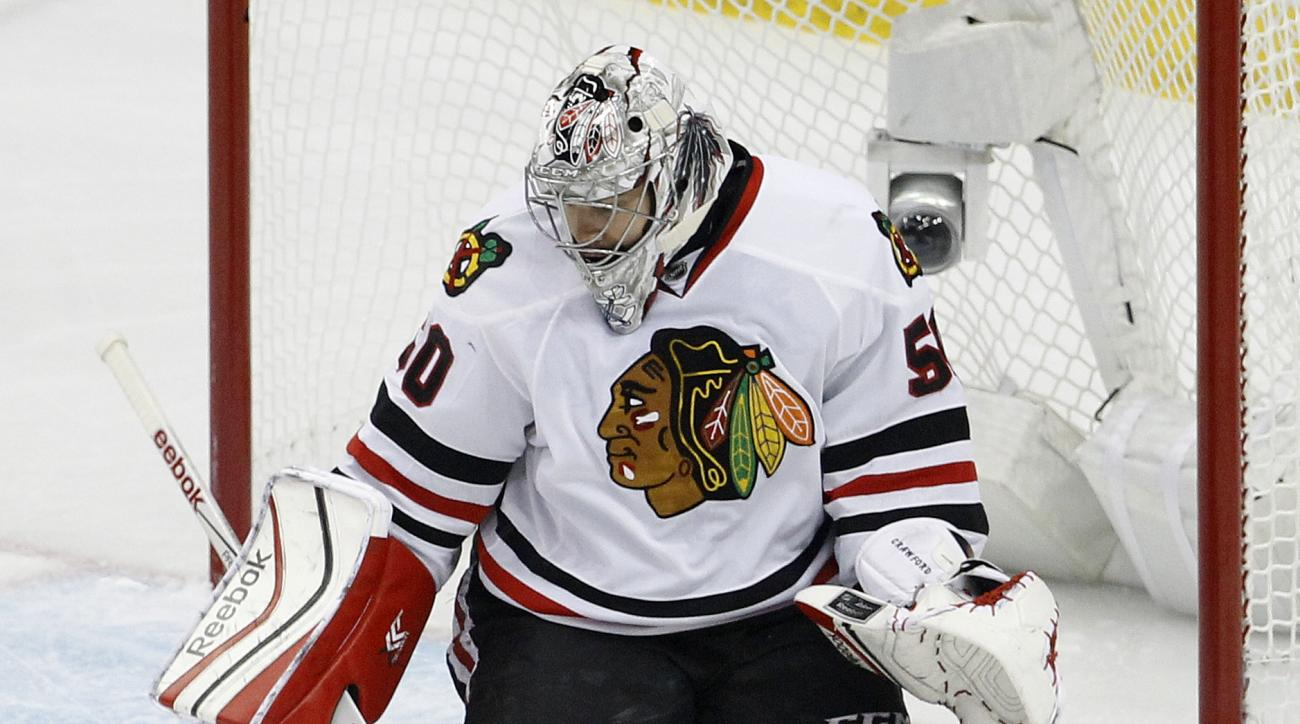 Chicago Blackhawks goalie Corey Crawford (50) swats away a shot by Minnesota Wild center Mikko Koivu (9), of Finland, during the first period of Game 4 in the second round of the NHL Stanley Cup hockey playoffs Thursday, May 7, 2015, in St. Paul, Minn. (A