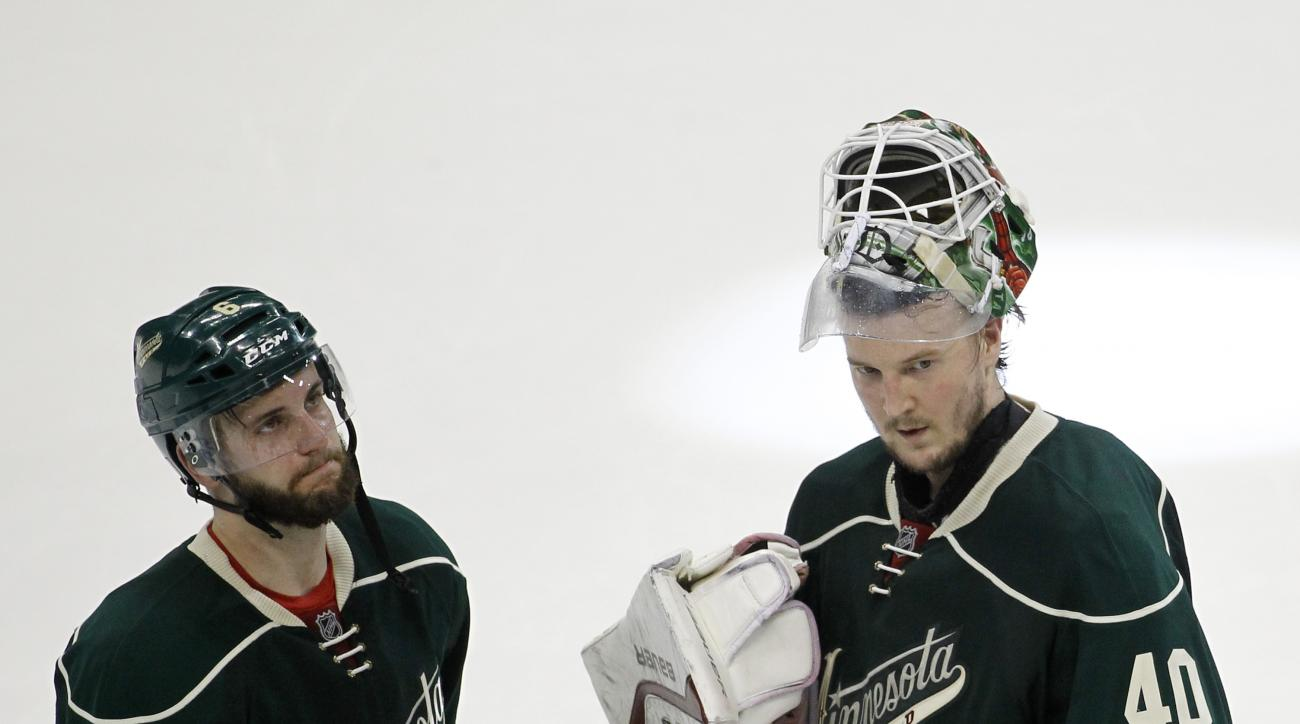 Minnesota Wild defenseman Marco Scandella (6) and goalie Devan Dubnyk (40) react after the Chicago Blackhawks defeated the Wild 4-3 in Game 4 in the second round of the NHL Stanley Cup hockey playoffs, Thursday, May 7, 2015, in St. Paul, Minn. (AP Photo/A