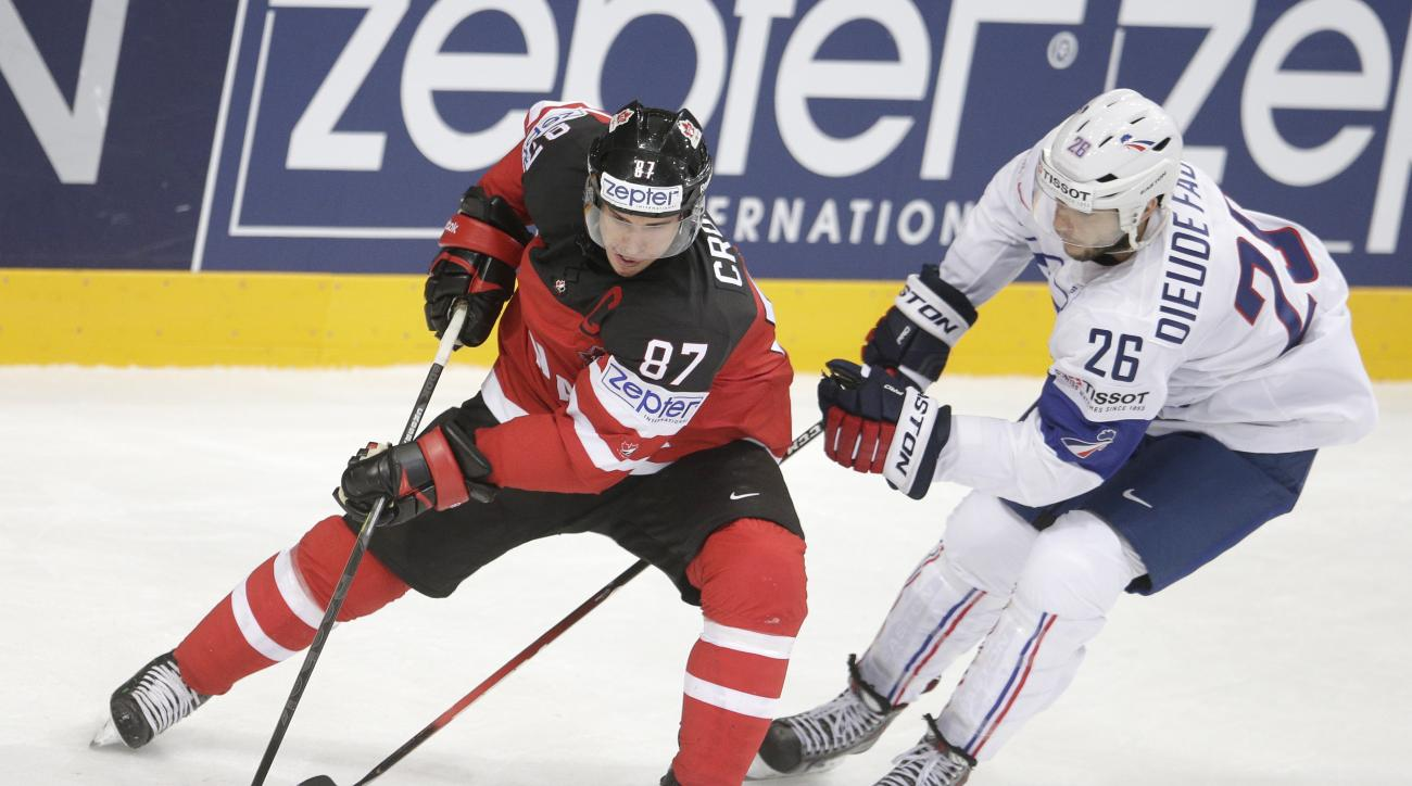 Canada's Sidney Crosby, left, challenges for the puck with France's Benjamin Dieude-Fauvel, right, during the Hockey World Championships Group A match in Prague, Czech Republic, Saturday, May 9, 2015. (AP Photo/Petr David Josek)