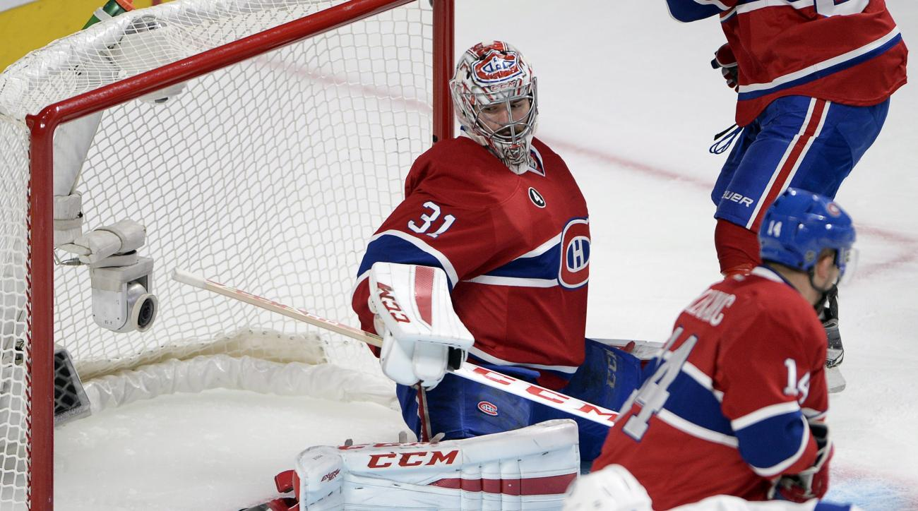 Montreal Canadiens goalie Carey Price (31) makes a pad-save on Tampa Bay Lightning left wing Brenden Morrow (10) as Canadiens center Tomas Plekanec (14) looks on during the second period of Game 5 of a second-round NHL Stanley Cup hockey playoff series Sa