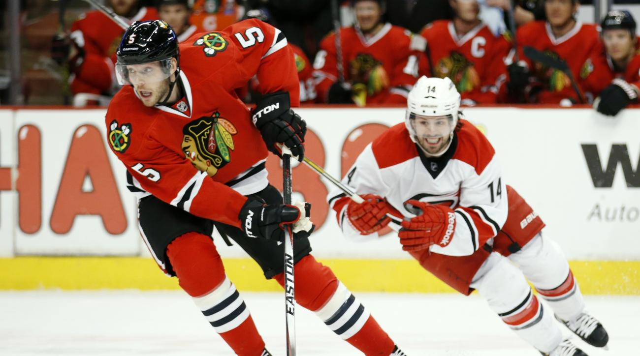 Chicago Blackhawks defenseman David Rundblad (5) advances past Carolina Hurricanes left wing Nathan Gerbe (14) during the first period of an NHL hockey game Monday, March 2, 2015, in Chicago. (AP Photo/Andrew A. Nelles)